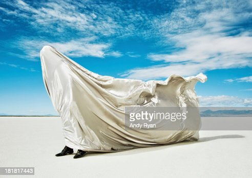 Man covered in fabric being blown by wind.