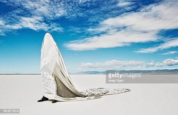 Man covered in fabric on salt flats.
