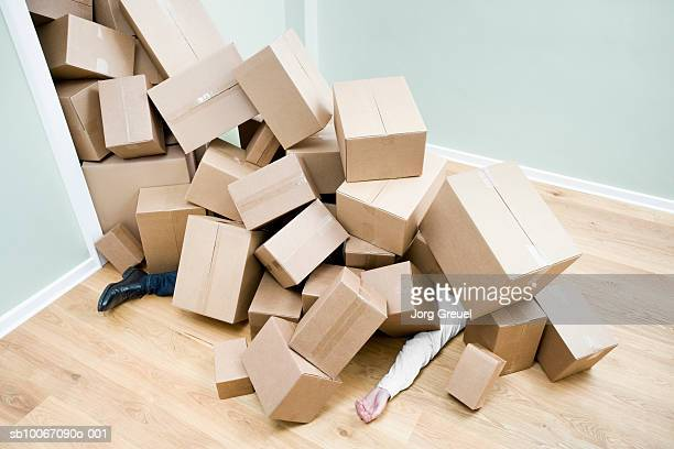 Man covered in pile of cardboard boxes