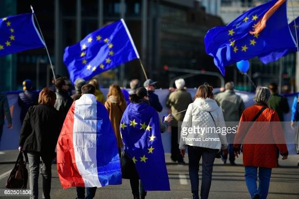 A man covered in the flag of the Netherlands and a woman covered with the flag of the European Union gather in the city center for a proEU...