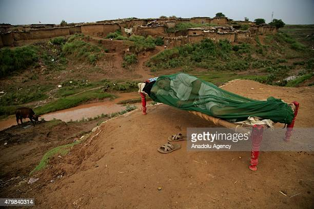 A man covered with a bednet sleeps outside his house because of the heatwave early in the morning in Islamabad Pakistan on July 8 2015