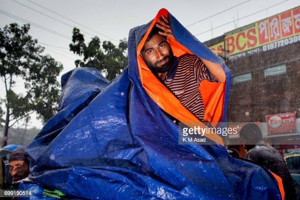 UNIVERCITY DHAKA BANGLADESH A man covered with plastic protect rainwater when heavy rainfall made in Dhaka city The death toll rises to 156 in...