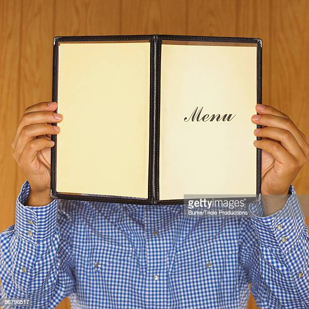 Man covering face with menu