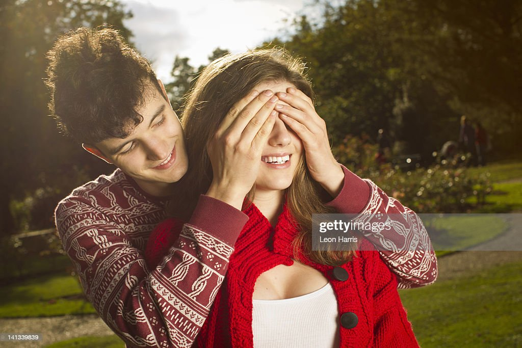 Man covering girlfriends eyes in park : Stock Photo
