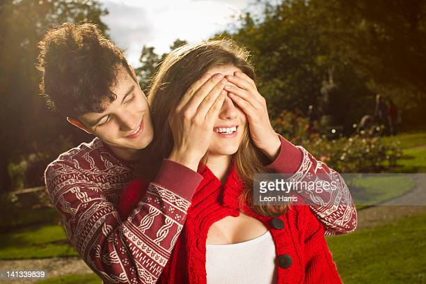 Man covering girlfriends eyes in park