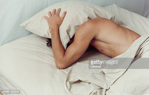 Man Covering Head with Pillow