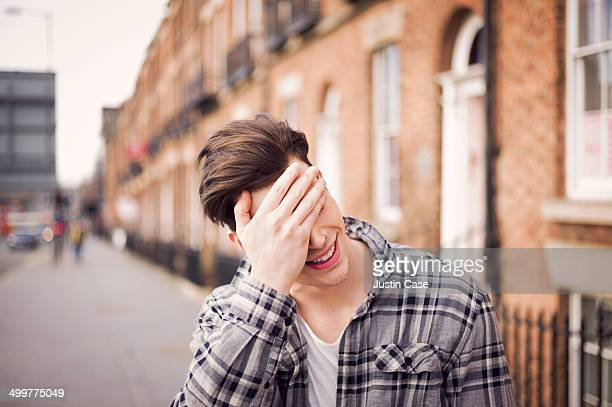 man covering his eyes in a laugh on the street