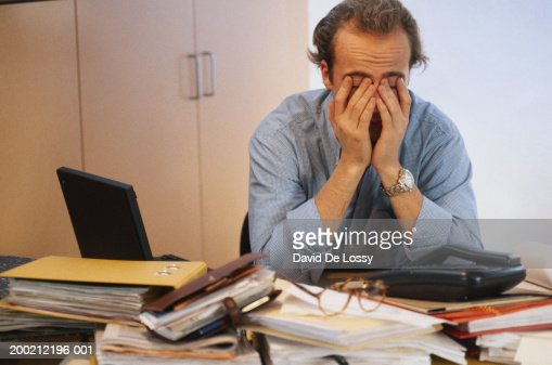 Man covering his face in office : Stock-Foto