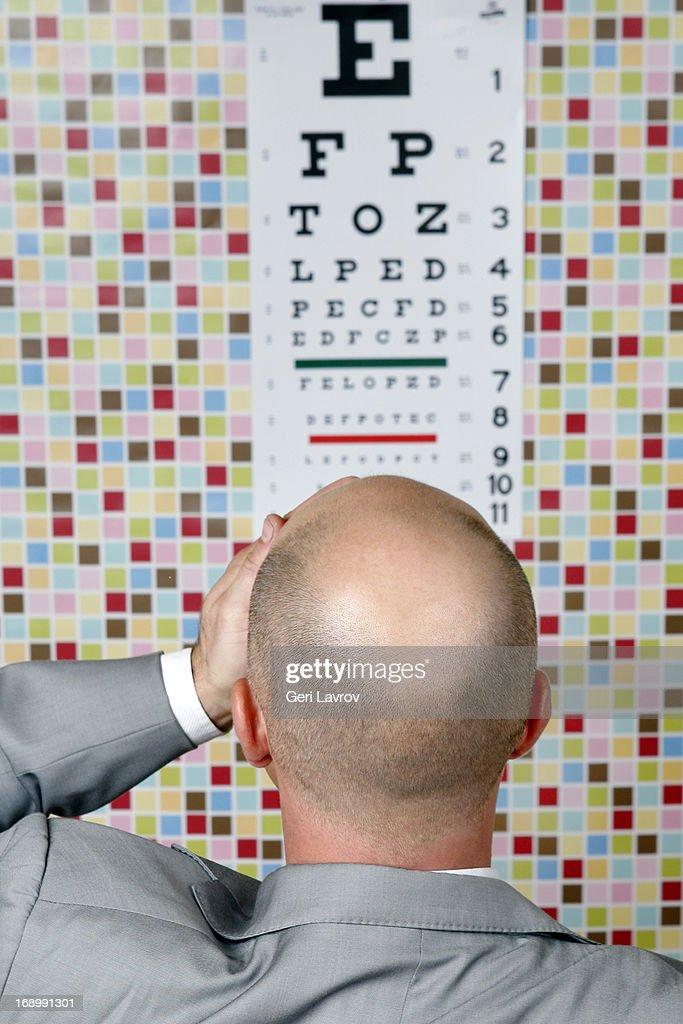 Man covering left eye reading an eye chart