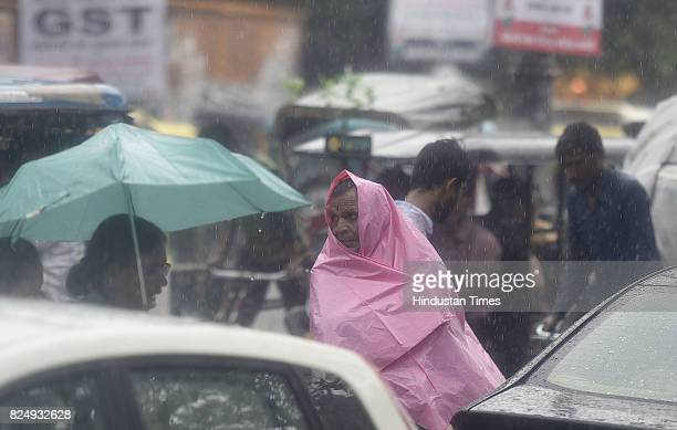 A man covers himself with a banner to keep himself dry from rain during the monsoon rain on July 31 2017 in New Delhi India Delhiites woke up to a...
