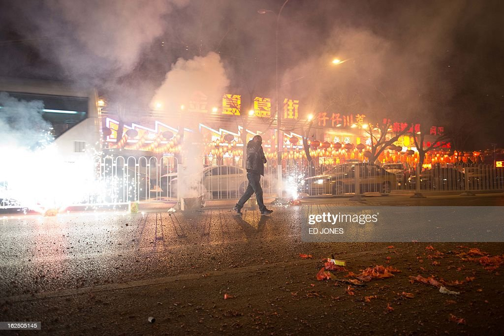 A man covers his ears as fireworks explode on a street in Beijing during the lantern festival, which marks the end of celebrations for the Chinese new year period, on February 24, 2013. China celebrated the traditional lantern festival with food and fireworks as millions of migrant workers flowed back to the cities and smog blanketed a large part of the country. AFP PHOTO / Ed Jones
