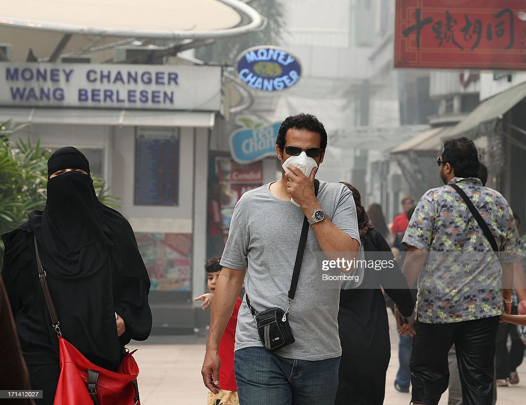 A man covers his face as he walks along a street in Kuala Lumpur, Malaysia, on Monday, June 24, 2013. Malaysia called for a meeting of Southeast Asian ministers as early as next week after haze from illegal Indonesian forest fires reached hazardous levels in parts of the region. Photographer: Goh Seng Chong/Bloomberg via Getty Images