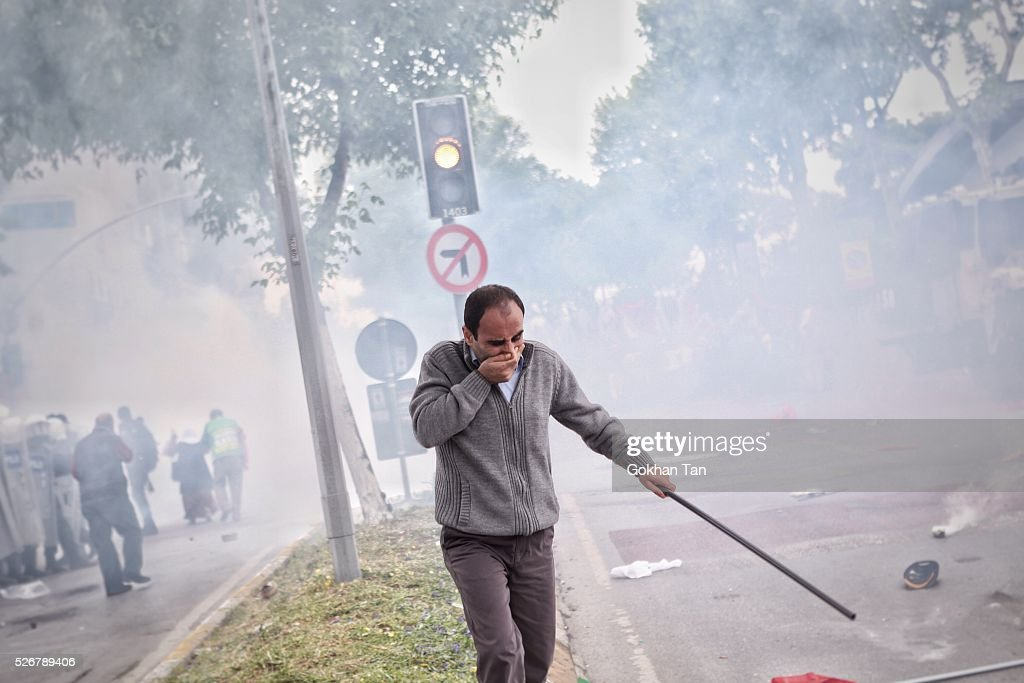 A man covers his face as Turkish anti-riot police fire tear gas during a May Day rally in Istanbul's Bakirkoy district on May 1, 2016 in Istanbul, Turkey. Turkish police used tear gas and water cannon to disperse protesters as they tried to make their way to Taksim Square and other protest points.