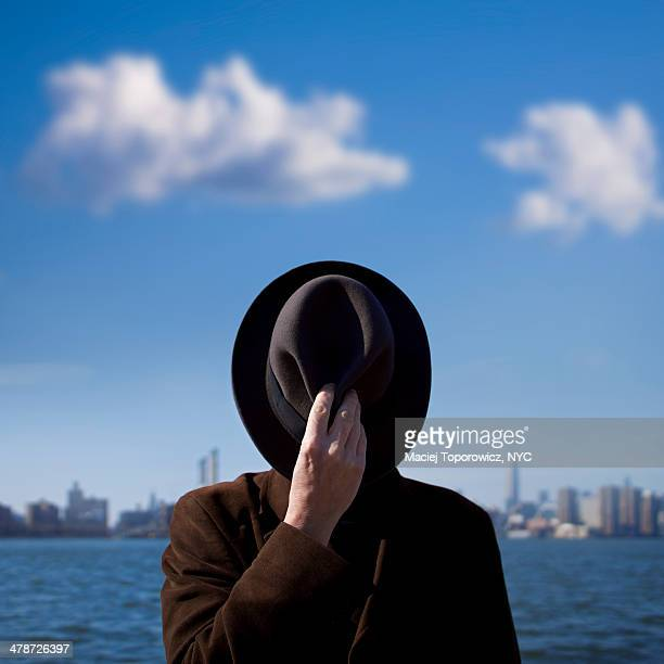 Man covers his face with hat.