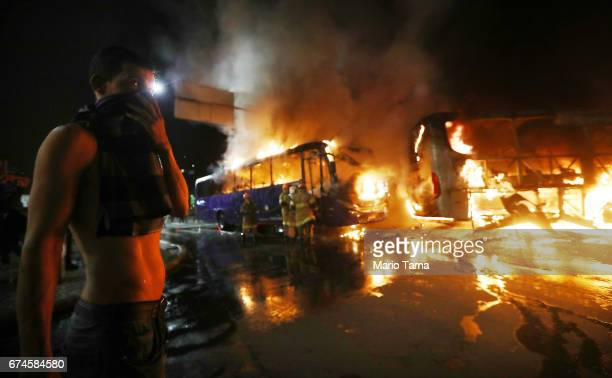 A man covers his faces as buses burn after being set on fire by protestors during a nationwide general strike on April 28 2017 in Rio de Janeiro...