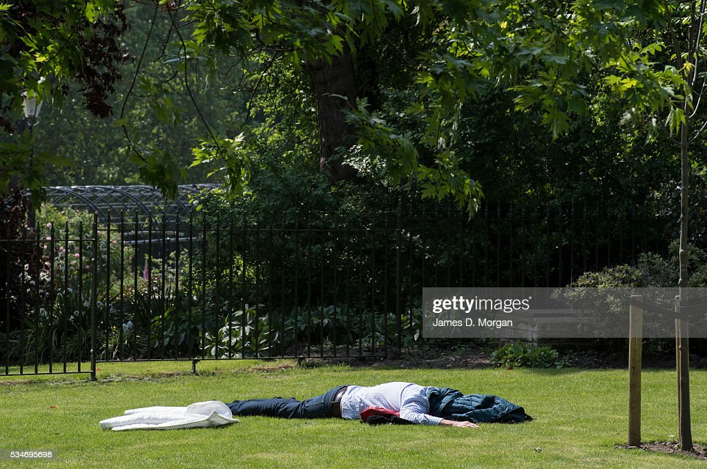 A man covers his head in the grass in Hyde Park ahead of the Bank Holiday weekend on May 27, 2016 in London, England. The weather today in London was warm and sunny with high temperatures expected to continue for the weekend.