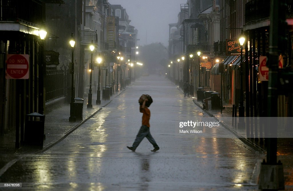 A man covers his head with a bag as he walks across a street in the French Quarter August 28, 2005 in New Orleans. Hurricane Katrina has sustained winds of 175 mph and is expected to make landfall in the Gulf Coast as early as August 29. Katrina killed at least seven when it moved through Miami-Dade County in Florida.