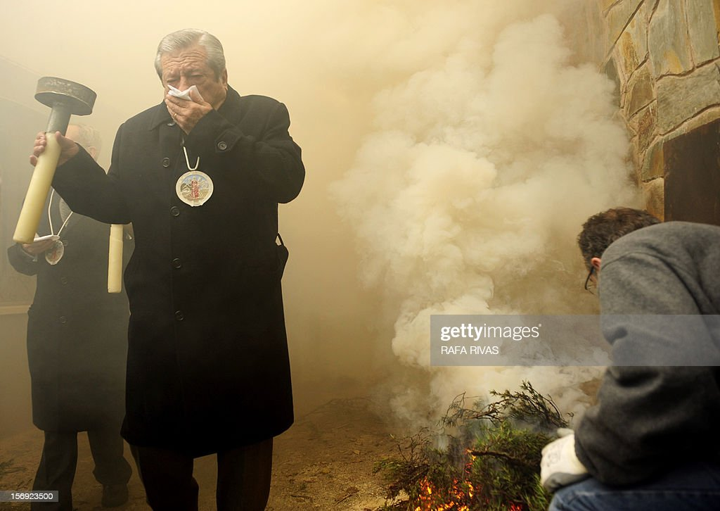 A man covers his mouth as he walks through the smoke of a bonfire with rosemary, on November 25, 2012, in the northern Spanish village of Arnedillo prior to celebratring the 'Procession of smoke'. Locals light bonfires to produce smoke that covers Arnedillo streets while the patron saint San Andres is carried in procession.