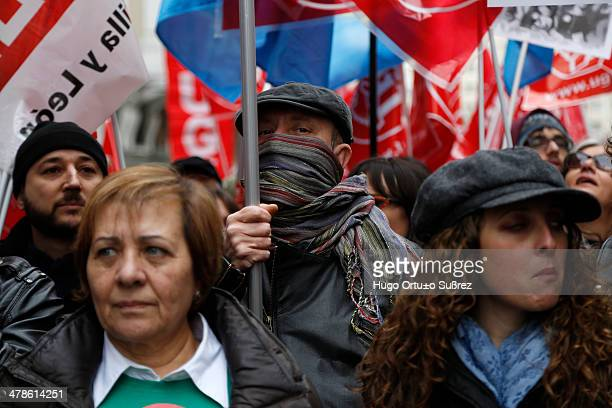 A man covers his mouth with a scarf from the intense cold during the protest against the Law for the Improvement of Educational Quality in Madrid...