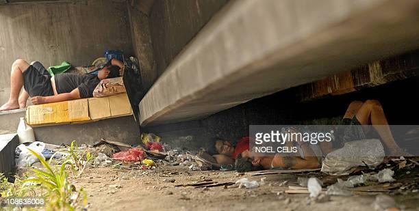 A man cradles a baby as he sleeps under the railway tracks of the Metro Rail Transit in Manila on January 31 2011 AFP PHOTO/NOEL CELIS