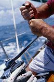 Man cranking capstan on sailboat, close-up