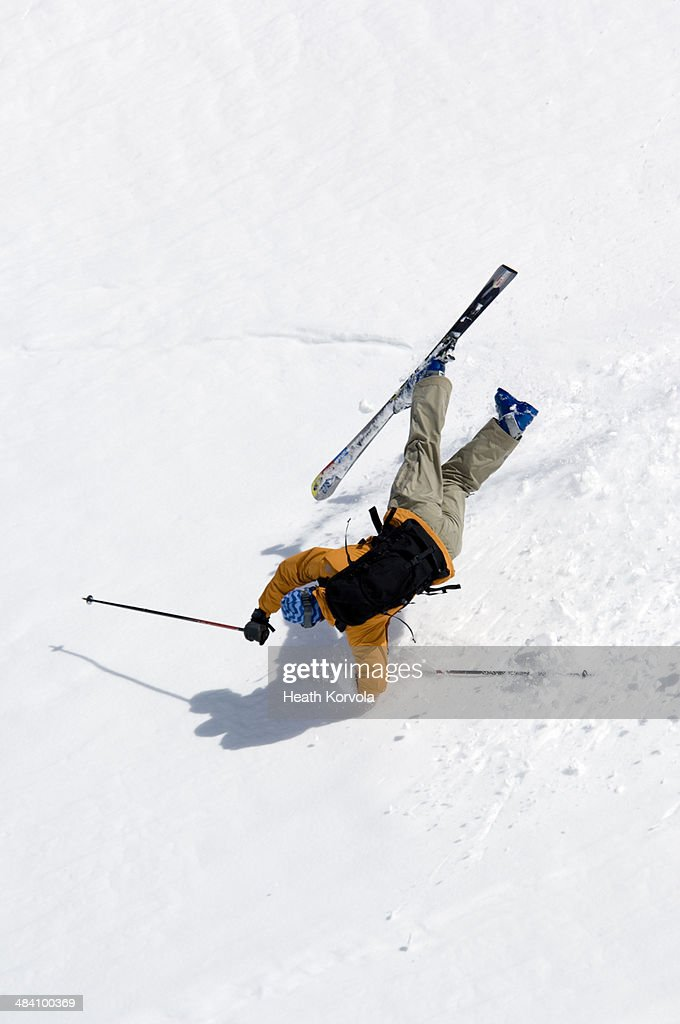 Man crashing head first on skis.
