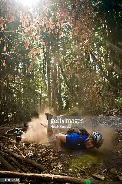Man crashing on mountain bike on single track.