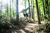 A man has mountain biking accident, flying over the handle bars of his bicycle.