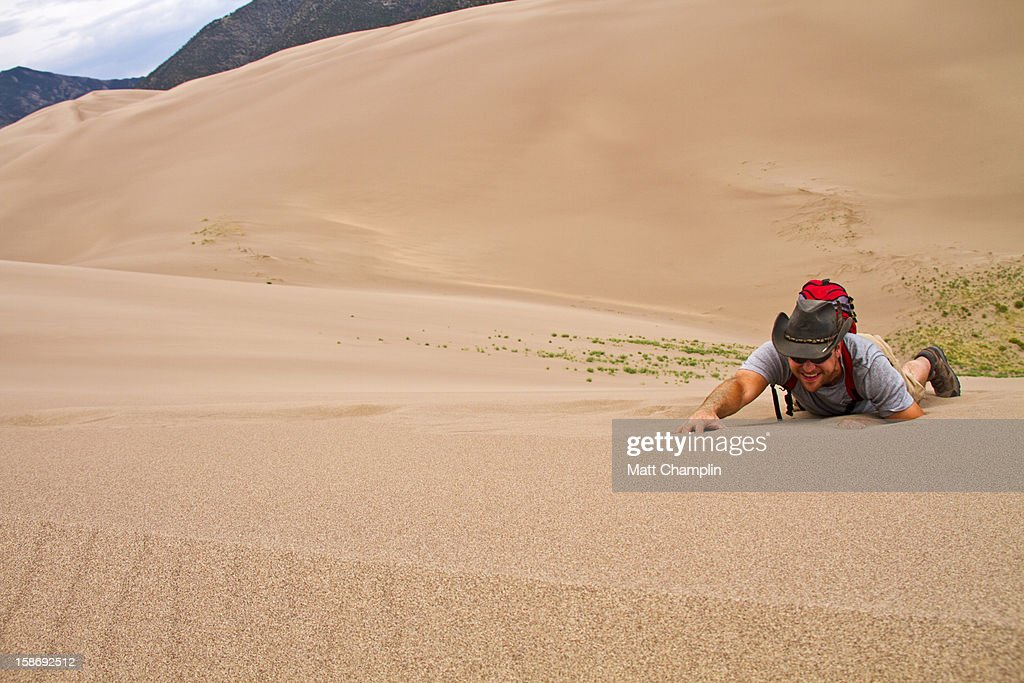 Man Crawling up side of Steep Sand Dune : Stock Photo