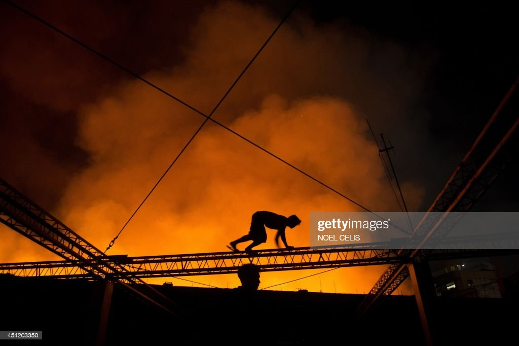 A man crawls on a truss of a building to witness a fire that engulfed a warehouse in Manila on August 26, 2014.