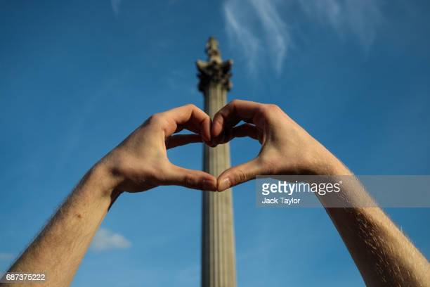 A man creates a heart symbol with his hands in front of Nelson's Column during a vigil for the victims of yesterday's Manchester Arena terror attack...