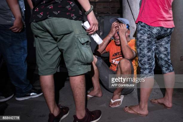 A man cries after seeing the body of his relative an alleged drug dealer killed during a police antidrug operation in Manila on August 17 2017 Police...