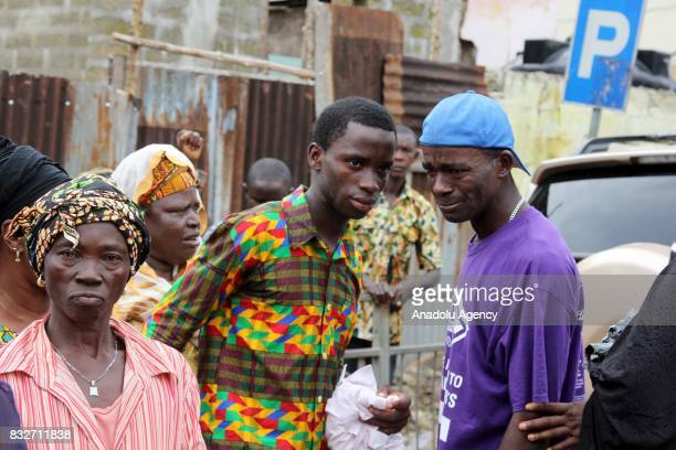 A man cries as people wait to identify their relatives' bodies at Connaught hospital after landslide struck the capital of the west African state of...