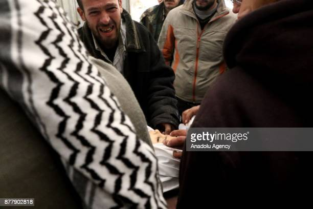 A man cries near the body of his relative after Assad regime's warplane carried out airstrikes over Arbin town of the Eastern Ghouta region in...