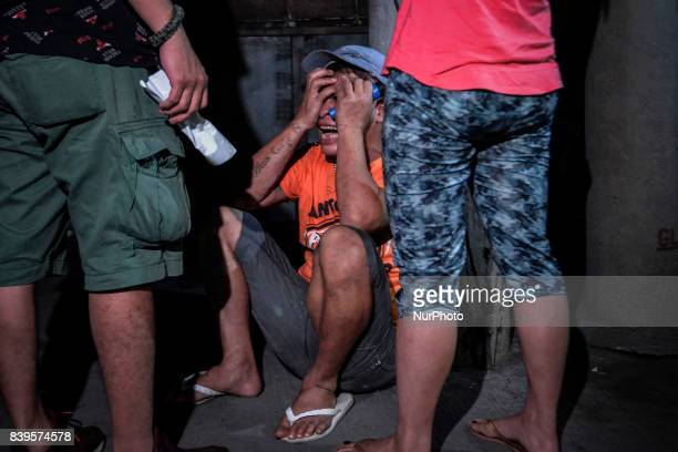 A man cries near the scene where his son killed after figuring in a shootout with police officers in Manila Philippines August 17 2017 Amidst the...