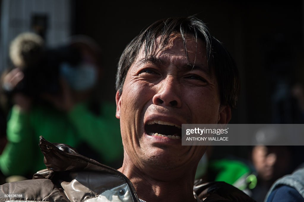 A man cries while asking a question during a briefing to relatives by Tainan's Mayor William Lai and Cheng Ming-chang, president of Tainan civil engineers association (both not seen), on the rescue operation of a building which collapsed in the 6.4 magnitude earthquake, in the southern Taiwanese city of Tainan on February 9, 2016. Rescuers deployed heavy machinery on February 9 in a renewed effort to locate more than 100 people trapped in the rubble of a Taiwan apartment complex felled by an earthquake as the 72-hour 'golden window' for finding survivors passed. AFP PHOTO / ANTHONY WALLACE / AFP / ANTHONY WALLACE