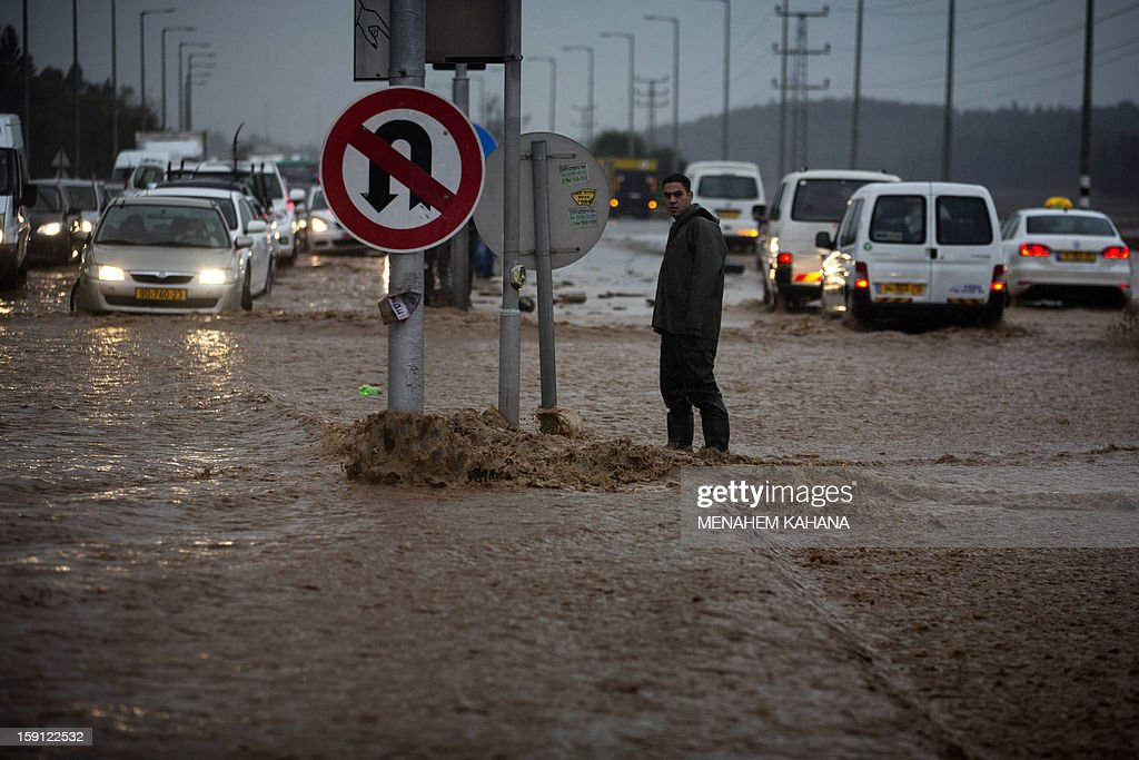 A man crosses a flooded road near the Israeli-Arab town of Kfar Qara, in central Israel, on January 8, 2013. Stormy weather, including high winds and heavy rainfall, lashed Israel and the Palestinian territories, downing powerlines and trees and blocking roads causing several injuries.