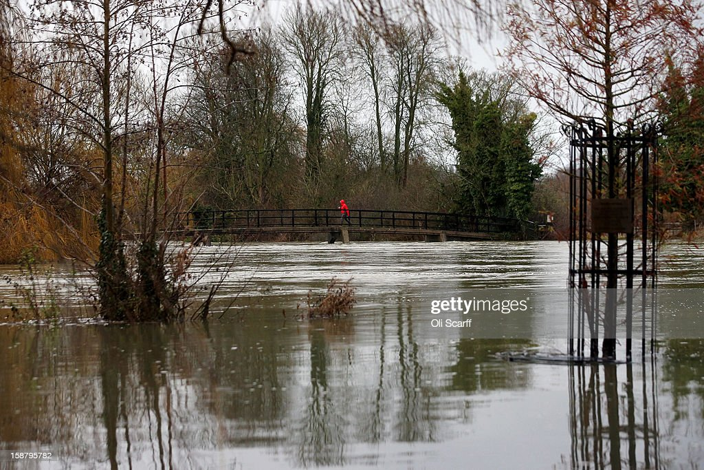 A man crosses a footbridge partially submerged by flood waters from the River Thames on December 29, 2012 in Sonning, England. The Environment Agency has issued widespread flood warnings across the UK whilst the Met Office has predicted further rain forecast for the remainder of 2012, which is likely to be recorded as the wettest year since records began in 1910.