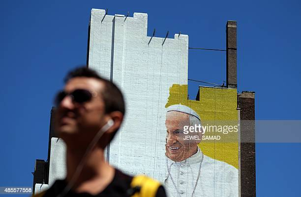 A man crosses a street as a partially completed mural of Pope Francis is seen on the wall of a highrise building in New York on August 28 2015 Pope...