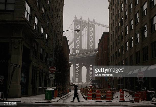 A man crosses a street near the Manhattan Bridge on the Brooklyn waterfront during a snowstorm December 26 2010 in New York City A winter storm...