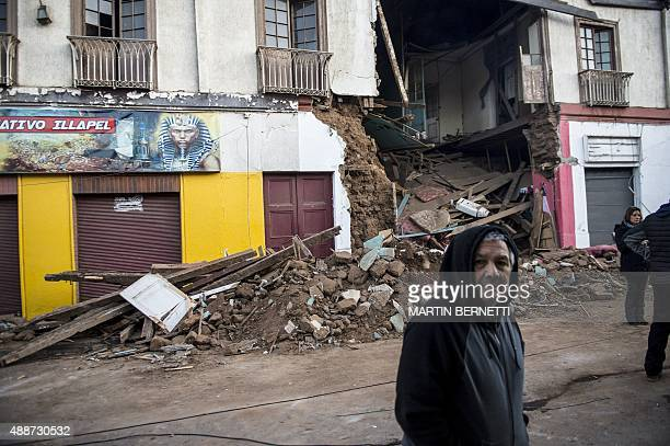 A man crosses a street next to a destroyed house after an earthquake in Illapel some 200 km north of Santiago on September 17 2015 A powerful...