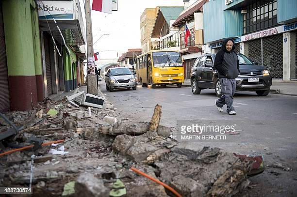 A man crosses a street next to rubble from a collapsed house after an earthquake in Illapel some 200 km north of Santiago on September 17 2015 A...