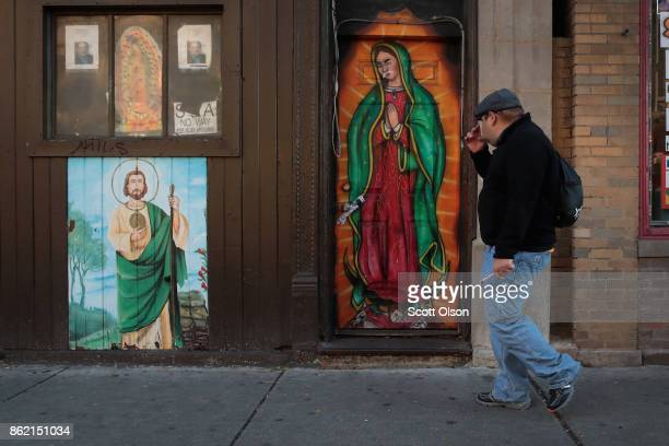 A man crosses himself as he walks past Christian murals painted on a storefront in the predominately Hispanic Pilsen neighborhood on October 16 2017...