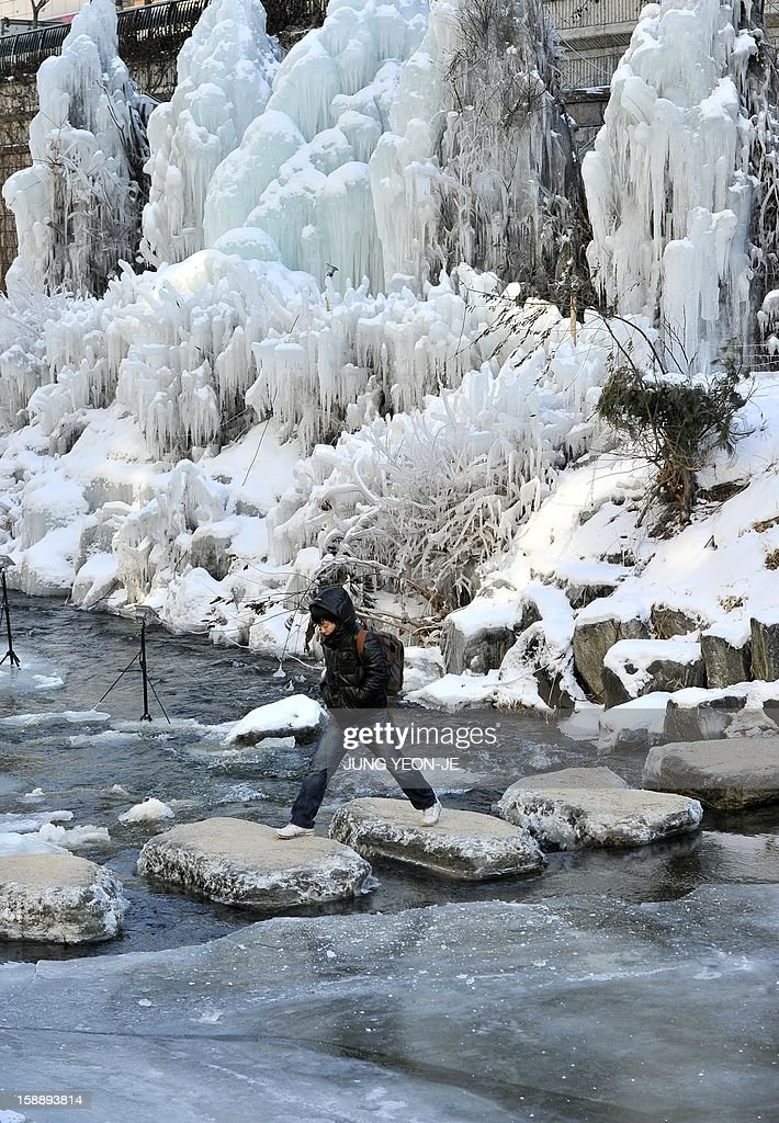 A man crosses the iced Cheonggye stream by the stepping stones in central Seoul on January 3, 2013. South Korea's electricity consumption shot up to a new all-time high on January 3, as temperatures dropped to this winter's lowest of 16.4 degrees Celsius (3 F) below zero in Seoul.
