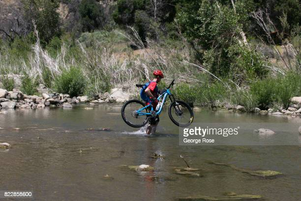 A man crosses the river near Rancho Oso Resort in Santa Barbara County's backcountry with a mountain bike on his shoulder on May 13 near Santa Ynez...