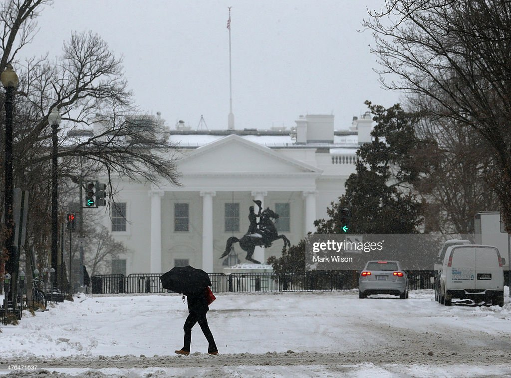 A man crosses the street as snow falls near the White House, on March 3, 2014 in Washington, DC. The federal governent is closed due to major snowstorm that is expected to dump up to a foot of snow in the Washington area.