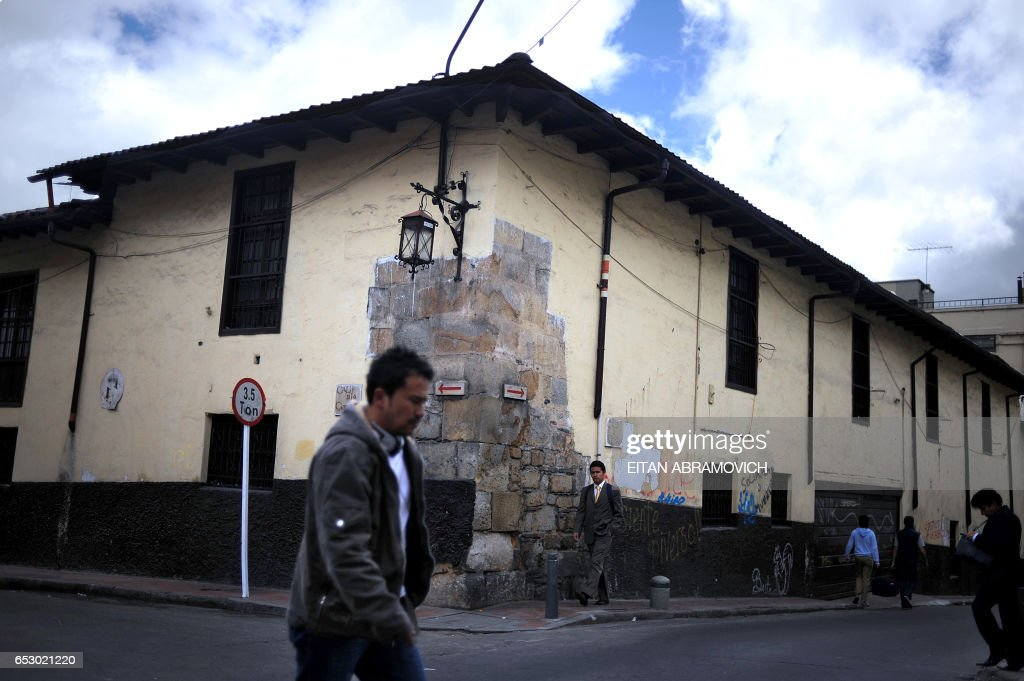 A man crosses the street in the historic neighborhood of La Candelaria in Bogota on September 17, 2009. La Candelaria is Bogota's oldest neighbourhood and the city's historical center, known for its colonial houses with wooden balconies and clay shingle roofs. AFP PHOTO/Eitan Abramovich /