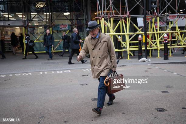 A man crosses the street outside Cannon Street Station on March 27 2017 in London England British Prime Minister Theresa May will trigger article 50...