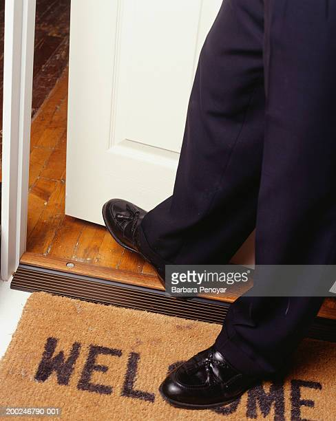 Man crossing doorway, Close-up of feet, (low section)
