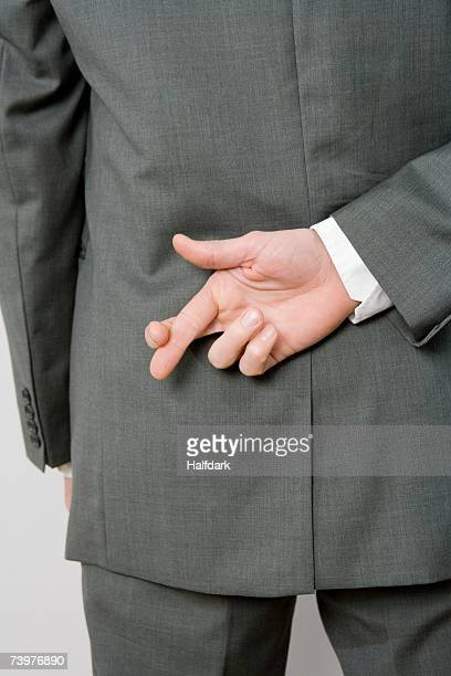 A man crossing his fingers behind his back